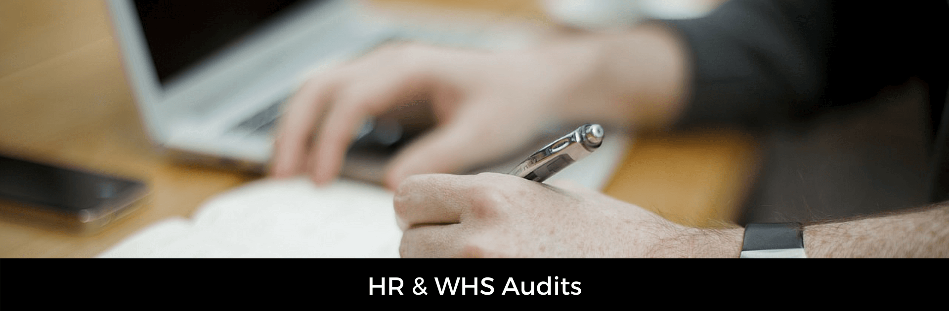 Image with caption HR & WHS audits. Background image of a person reviewing a document with a laptop in background.