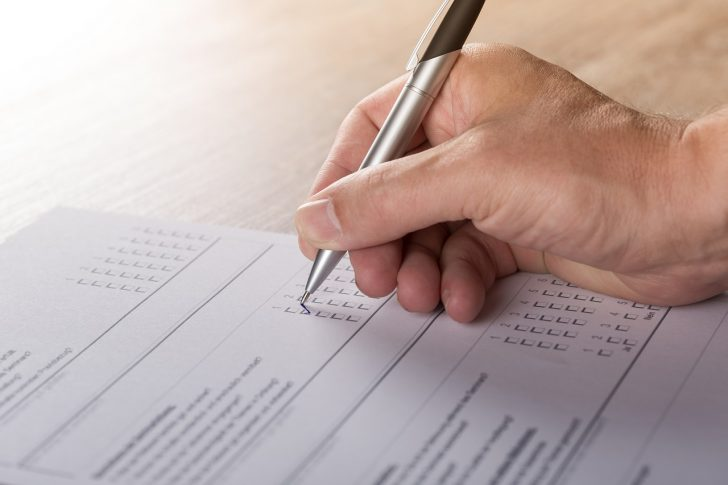 Picture of person completing a survey. Only hand is visible.