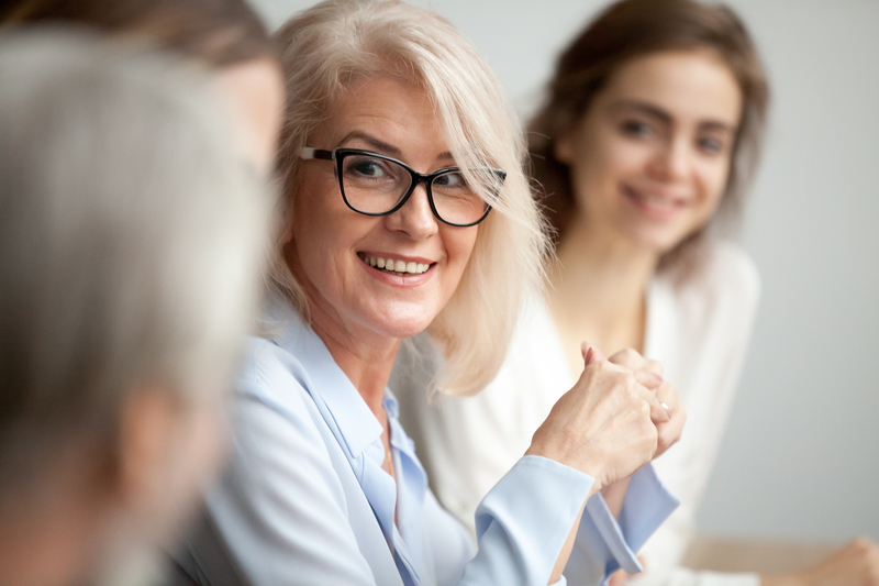 Smiling mature businesswoman in glasses looking at colleague at team meeting, happy attentive female team leader listening to new project idea, coach mentor teacher excited by interesting discussion
